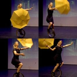 female unicyclist performs a balancing act with a yellow umbrella on stage in London